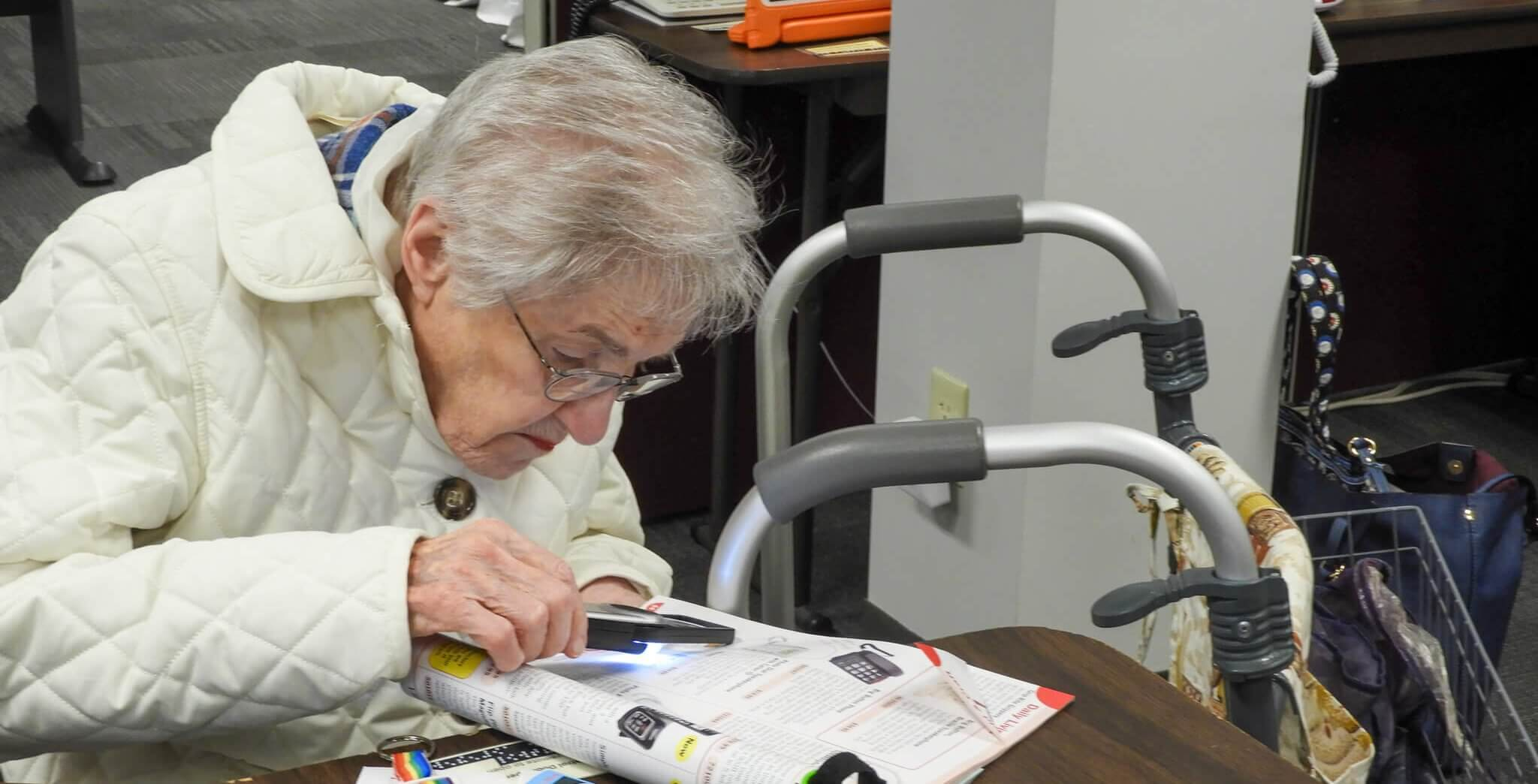 Older woman using a lighted magnifying glass to read
