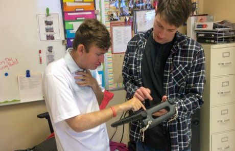 Young male assistant helping a young man using assistive technology
