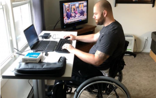 Man in a wheelchair sitting at a desk with a laptop