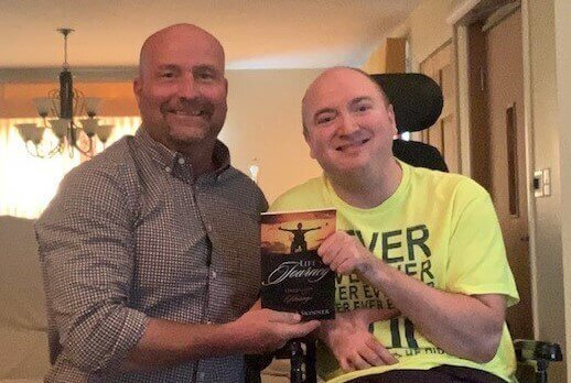 Picture of Mark McCabe on the left and Colten Skinner on the right holding Colten's book, Life's A Journey: Hardships to Blessings.