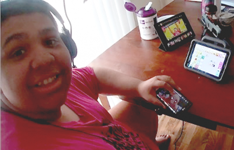 Young man wearing headphones using an AAC device
